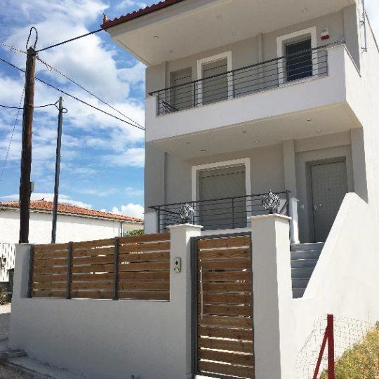 Διώροφη μονοκατοικία με πόρτα αλουμινίου και επένδυση πέτρας, ξύλου και αλουμινίου στους εξωτερικούς χώρους