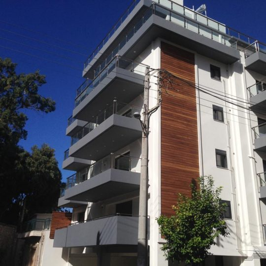 Μοντέρνα πολυκατοικία με εξωτερική διακόσμηση με ξύλο ιρόκο και γκρι κάγκελα αλουμινίου και γυαλιού
