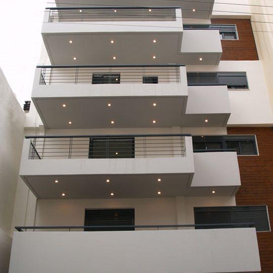 Πρόσοψη πολυκατοικίας με φωτισμό και ξύλο ιρόκο