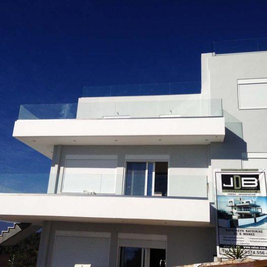 Διώροφη κατοικία με γυάλινα κάγκελα και άσπρα αλουμίνια
