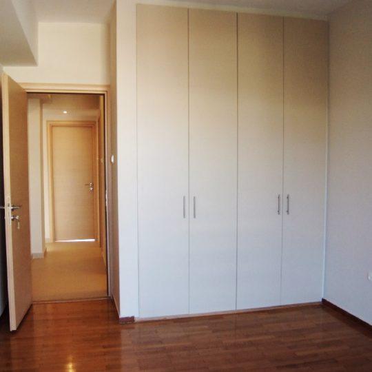Δωμάτιο με ξύλινο δάπεδο και εντοιχισμένες δίφυλλες ντουλάπες