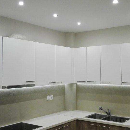 Κουζίνα με gloss white πορτάκια σε συνδυασμό με ξύλο και ταινία led κάτω από τα ντουλάπια