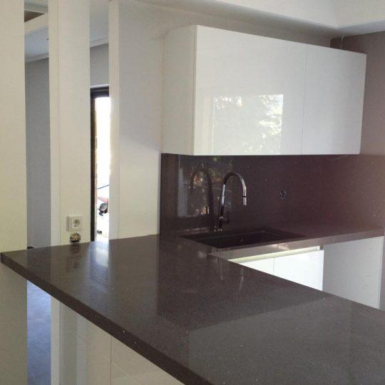 Διακόσμηση κουζίνας με κολώνες από γυψοσανίδα, κρυφό φωτισμό και πάγκο τεχνογρανίτη